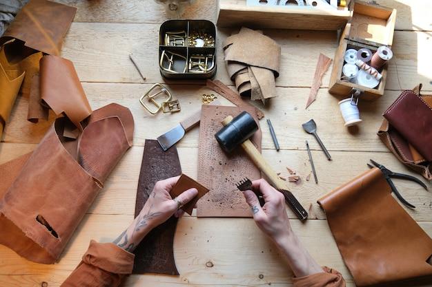 ワークショップの彼のテーブルで革と作業工具を使用して作業している労働者の高角度のビュー