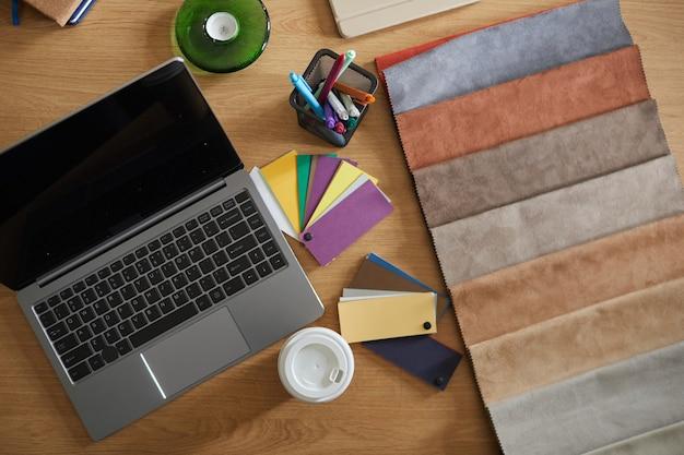 노트북 및 패브릭 샘플이있는 디자이너의 작업장 높은 각도보기