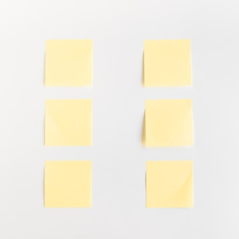 High angle view of yellow adhesive notes arranged in a row on white background
