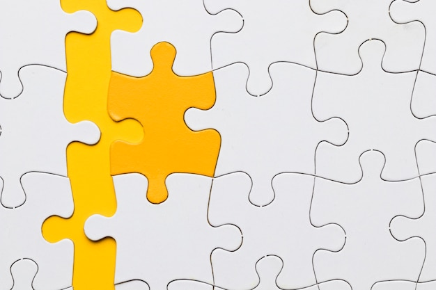 흰색 조각으로 배열 된 노란색 퍼즐 조각의 높은 각도보기