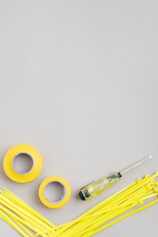 전기 테스터 드라이버가있는 노란색 테이프 및 나일론 지퍼 와이어의 높은 각도보기