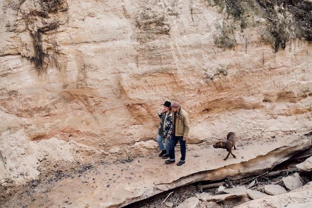 手をつないで、岩の間で屋外で犬と一緒に歩いている若いカップルの高角度のビュー