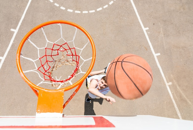 농구를 하는 젊은 남자의 높은 각도 보기, 농구를 하는 남자의 후프 위에서 보기