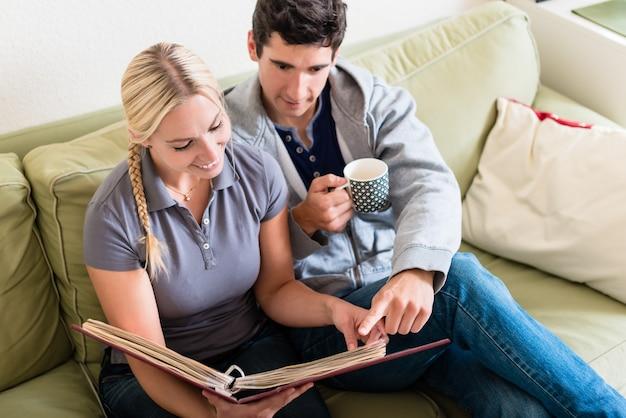 自宅のソファで一緒に写真アルバムを見ながら笑っている若い懐かしいカップルのハイアングルビュー