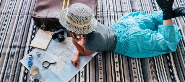 모자를 쓴 젊은 여성이 커피 컵과 함께 카펫에 누워 아틀라스를 바라보는 높은 각도. 종이에 돋보기로 지도상의 위치를 계획하는 젊은 여성. m을 사용하여 휴가를 계획하는 여성