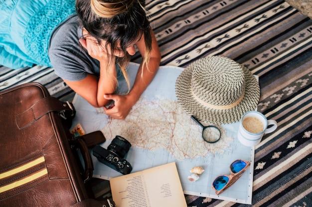 커피 컵과 함께 카펫에 누워 아틀라스를 보고 젊은 여자의 높은 각도 보기. 종이에 돋보기로 지도상의 위치를 계획하는 젊은 여성. 지도를 보고 휴가를 계획하는 여자