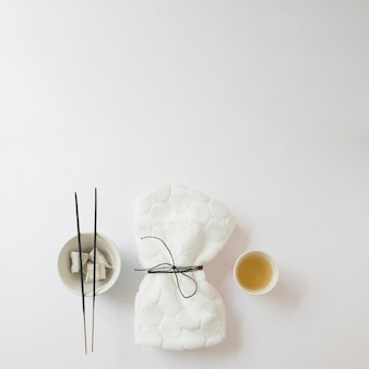 High angle view of oil; incense stick; pumice stone and tied napkin on white background