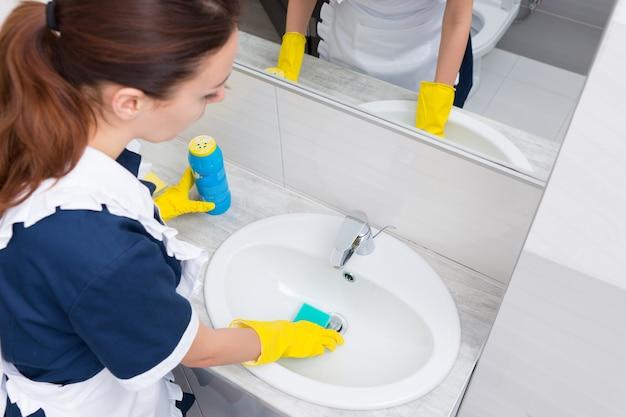 青いスポンジとスクラブパウダーでシンクを掃除する黄色のゴム手袋で家政婦の高角度のビュー