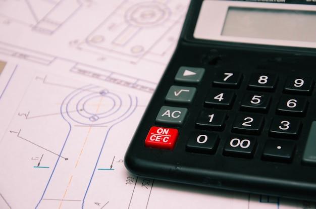 Вид под высоким углом на план электромонтажа с калькулятором