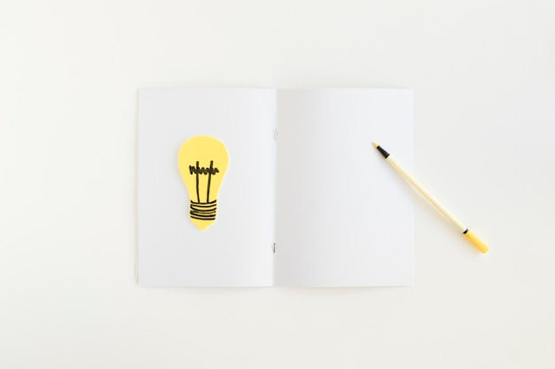 High angle view of pen and light bulb on card