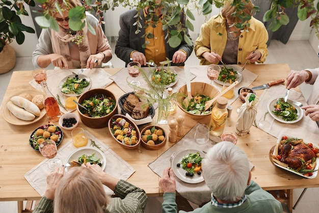 High angle view of people sitting at dining table with different dishes and having dinner together