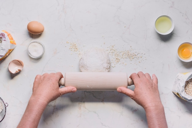 High angle view of a person's hand flattening dough with rolling pin
