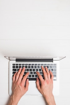High angle view of a person's hand working on laptop over wooden desk