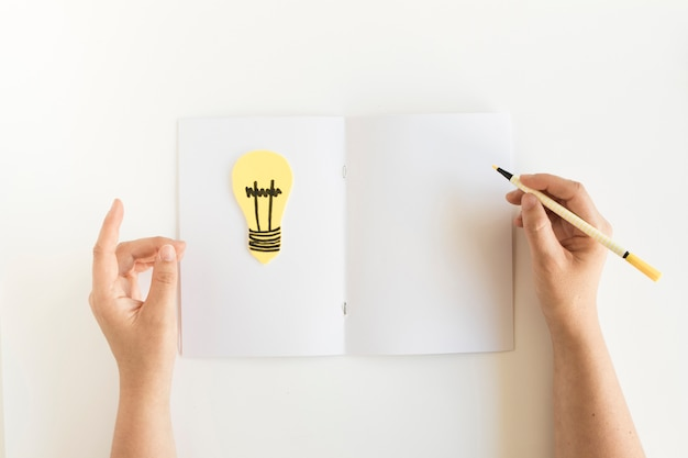 High angle view of a person's hand writing on card with light bulb