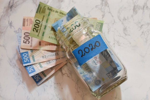 High angle view of pesos in a jar with a blue [2020] label on it on the table under the lights