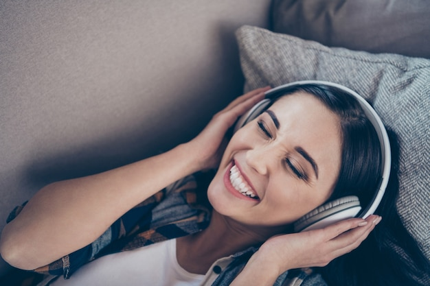 High angle view photo of amazing lady in high spirits listening favorite radio fm in modern earflaps lying comfortable sofa wearing casual clothes apartment indoors