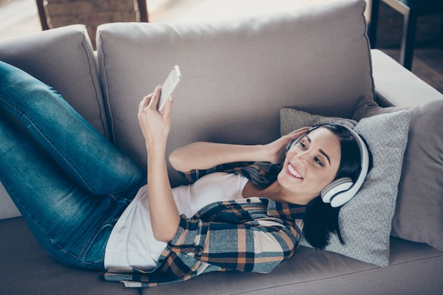 High angle view photo of charming lady holding telephone listen modern earflaps choosing audio lying comfort sofa wear casual checkered shirt apartment indoors
