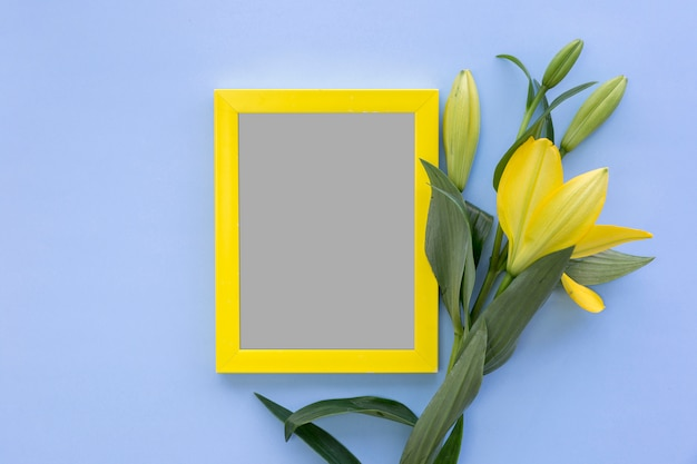 High angle view of photo frame and yellow lily flowers on blue colored backdrop