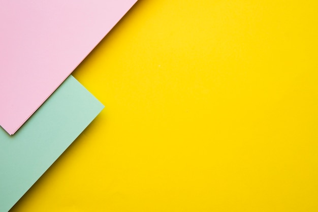 High angle view of pink and green cardboard papers on yellow backdrop