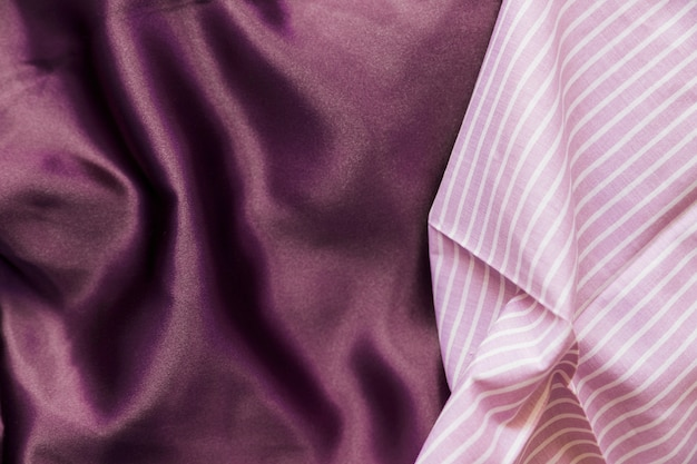 High angle view of pink line pattern and plain purple textile