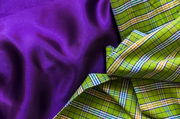 High angle view of plaid cotton cloth on plain purple textile