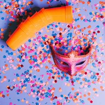 High angle view of plastic glasses and elegant party mask with confetti on blue background