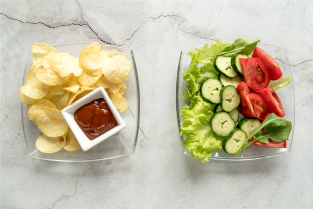 High angle view of potato chips with sauce and vegetable salad on glass bowl