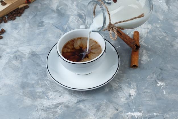 Vista di alto angolo versando il latte in una tazza di caffè con chicchi di caffè, bastoncini di cannella su sfondo grigio sgangherata. orizzontale