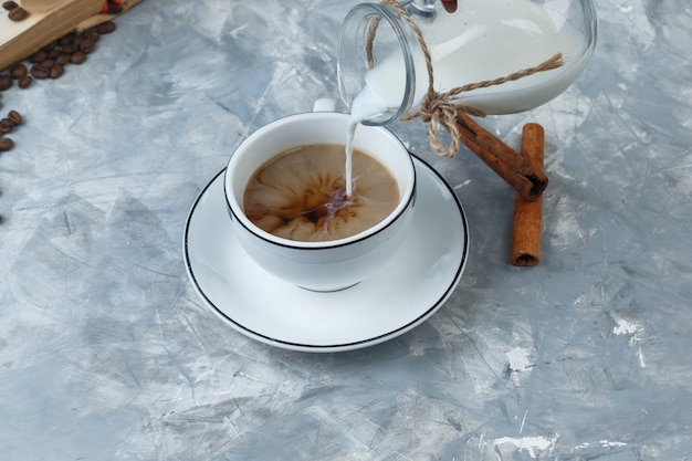 High angle view pouring milk into a cup of coffee with coffee beans, cinnamon sticks on grungy grey background. horizontal