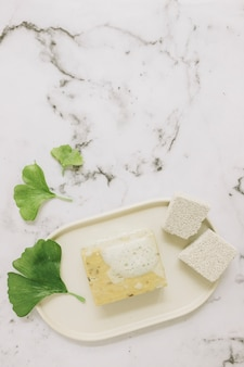High angle view of pumice stone; soap and gingko leaf on marble background