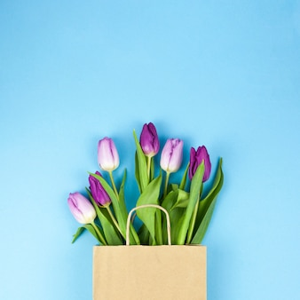 High angle view of purple tulip flowers on brown bag against blue backdrop