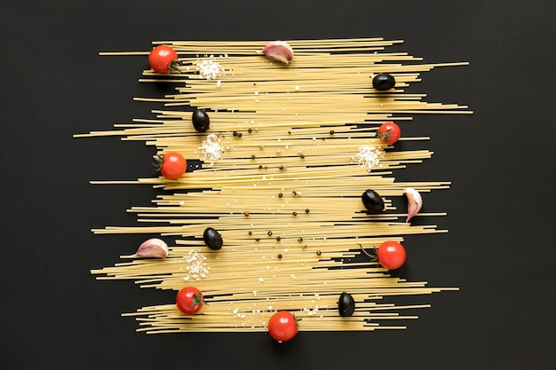High angle view of raw spaghetti pasta; cherry tomato; black olive and black pepper arranged on black surface