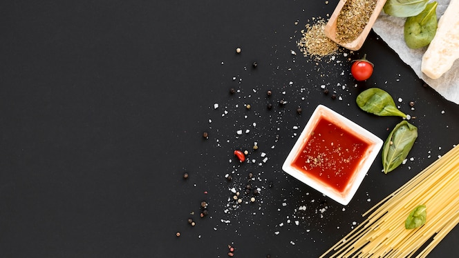 High angle view of raw spaghetti pasta and ingredient on slate backdrop