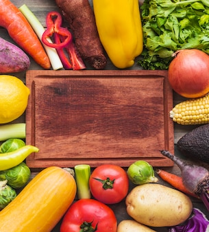 High angle view of raw vegetables surrounding wooden chopping board