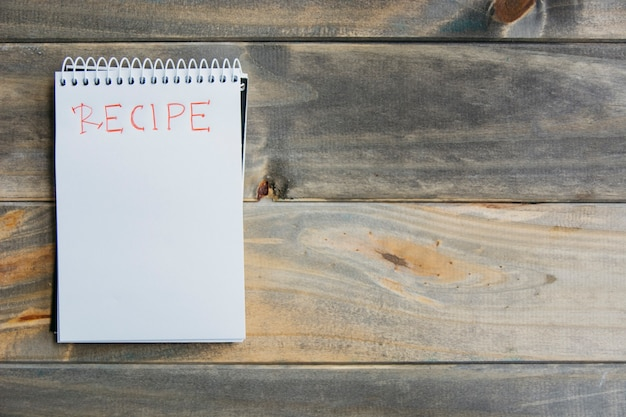 High angle view of recipe word on spiral notepad over wooden background