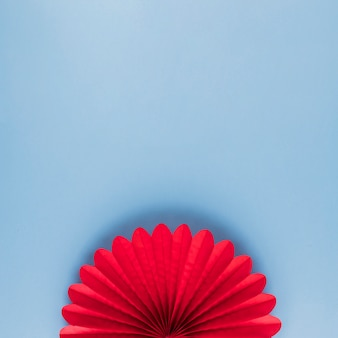 High angle view of red beautiful origami flower on blue backdrop