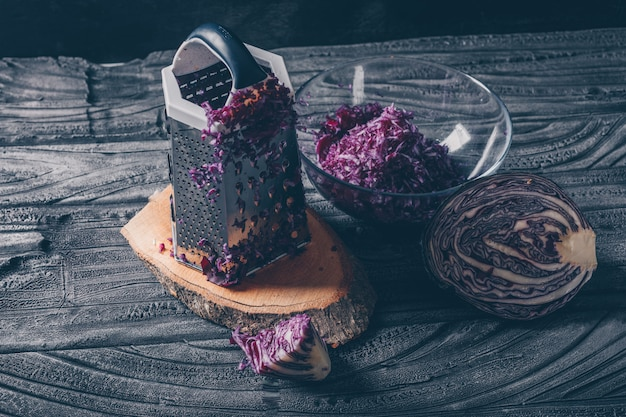 High angle view red cabbage with vegetable grater and grated cabbage on dark wooden background. horizontal