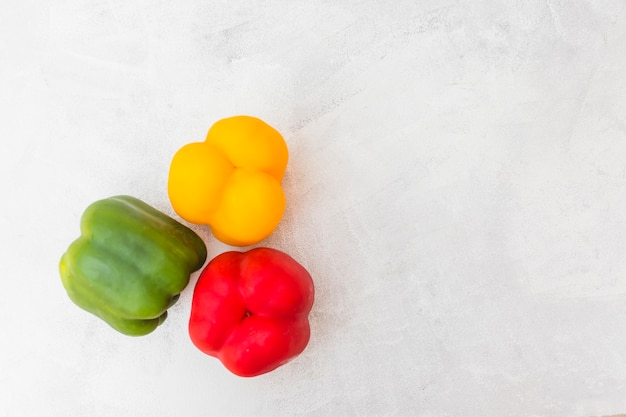 High angle view of red; green and yellow bell peppers on white background