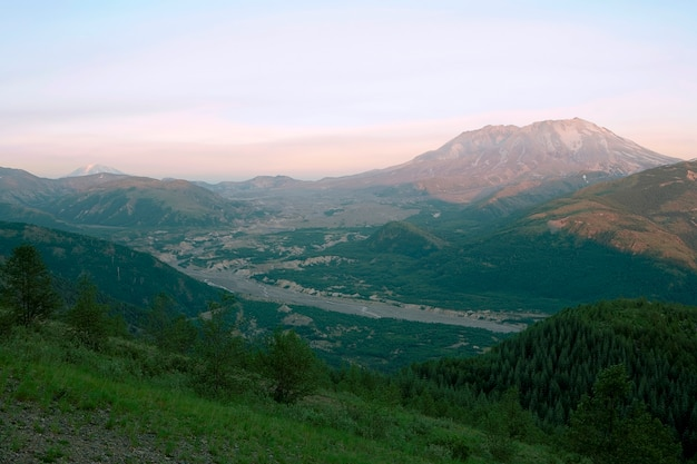 High angle view of remote river valley, rolling landscapes and mountains in the distance