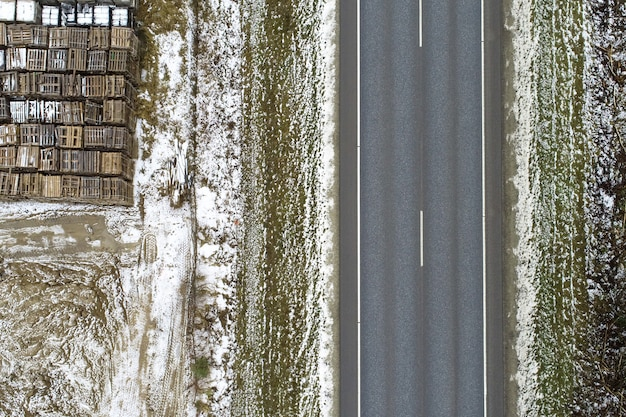 High angle view of a road surrounded by a meadow covered with the snow with metallic objects on it