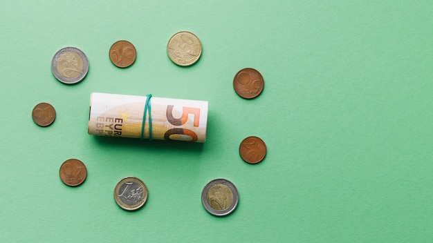 High angle view of rolled up euro bank note with coins on green background