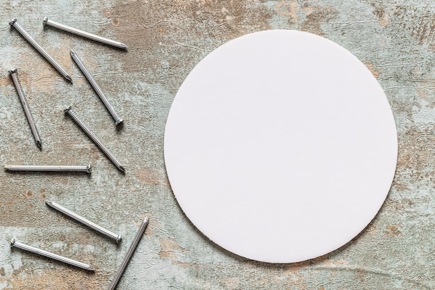 High angle view of round white circular frame and nails on grunge wooden desk