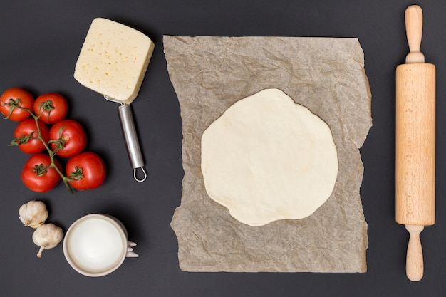 High angle view of row ingredient and rolled out pizza dough on parchment paper with wooden rolling pin over black surface