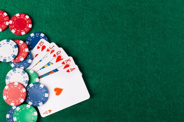 High angle view of royal flush clubs and chips on green poker table