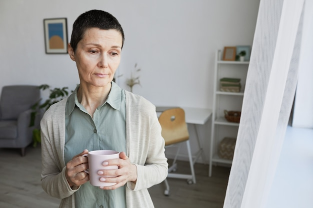 High angle view at sad mature woman standing by window at home and drinking coffee, covid, social distancing concept