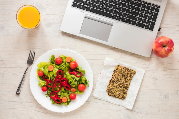 High angle view of salad; juice; granola bar; fruits with laptop on table