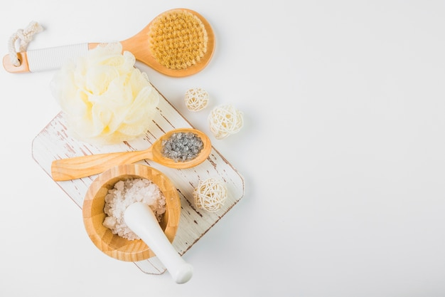 High angle view of salt; loofah and brush on white backdrop