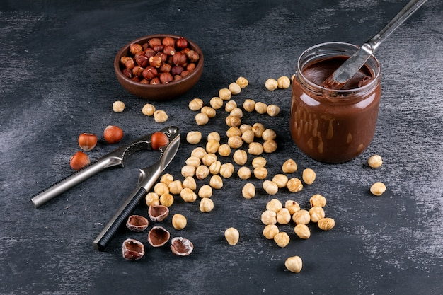 High angle view scattered cleaned hazelnuts in brown bowl with cocoa spread and nutcracker on dark stone table. horizontal