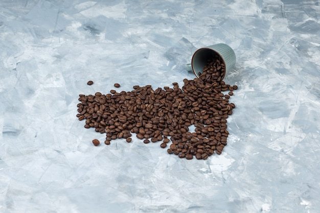 High angle view scattered coffee beans from cup on grey plaster background. horizontal