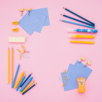 High angle view of school supplies over pink wallpaper